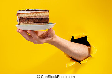 Hand holding a piece of cake on a plate through a torn hole in yello background