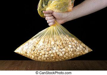 hand holding a plastic bag of popcorn