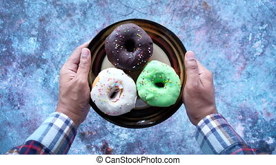 Close up of hand holding donuts