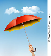 Hand holding a red and yellow umbrella against a blue sky with c