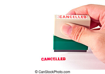 Hand holding a rubber stamp with the word Cancelled