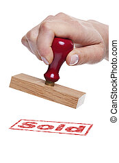 Hand holding a rubber stamp with the word Sold