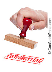 Hand holding a rubber stamp with the wordConfidential