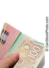 Hand holding a series of Canadian banknotes with 100 dollars on top