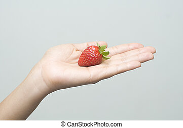 hand holding a single strawberry