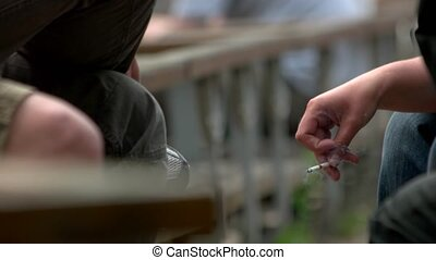 Hand holding a smoking cigarette.