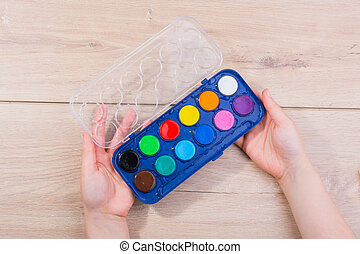 Hand holding a watercolor paint box on  wooden background
