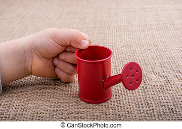 Hand holding a watering can on canvas background - Hand...