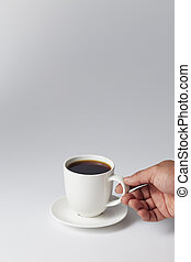 Hand holding a white cup of coffee