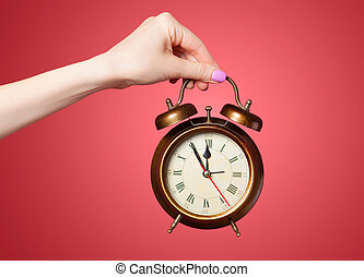 Hand holding alarm clock on red background.