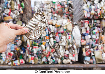 Hand holding aluminum can for recycle