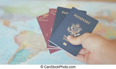 FHD Video of a Hand Holding American and Swedish Passports with a Blurry and Colorful World Map as Background