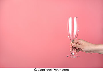 Hand holding an empty champagne glass on a pink background.