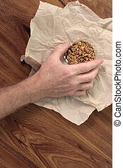 Hand Holding an Open Granola Mix Snack Container over a Napkin
