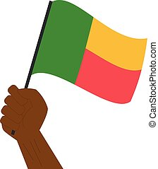 Hand holding and raising the national flag of Benin