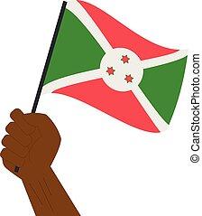Hand holding and raising the national flag of Burundi
