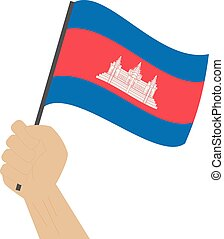 Hand holding and raising the national flag of Cambodia