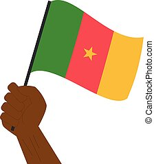 Hand holding and raising the national flag of Cameroon