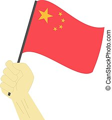 Hand holding and raising the national flag of China