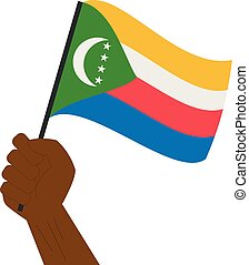 Hand holding and raising the national flag of Comoros