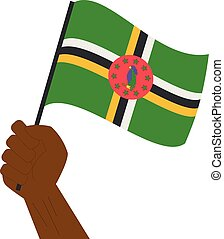 Hand holding and raising the national flag of Dominica