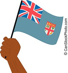 Hand holding and raising the national flag of Fiji
