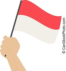Hand holding and raising the national flag of Indonesia