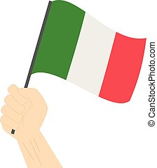 Hand holding and raising the national flag of Italy
