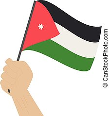 Hand holding and raising the national flag of Jordan