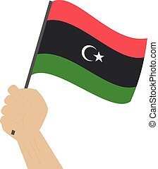 Hand holding and raising the national flag of Libya