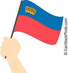 Hand holding and raising the national flag of Liechtenstein
