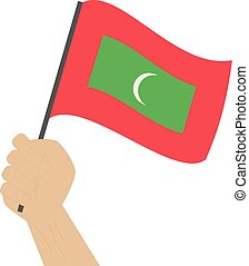 Hand holding and raising the national flag of Maldives