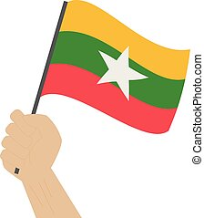 Hand holding and raising the national flag of Myanmar