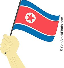 Hand holding and raising the national flag of North Korea