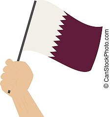 Hand holding and raising the national flag of Qatar