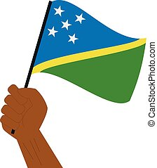 Hand holding and raising the national flag of Solomon...
