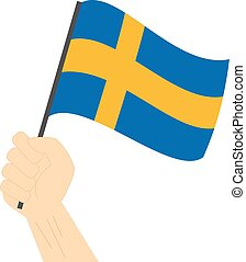 Hand holding and raising the national flag of Sweden