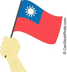 Hand holding and raising the national flag of Taiwan