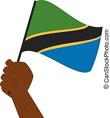 Hand holding and raising the national flag of Tanzania