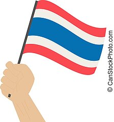 Hand holding and raising the national flag of Thailand