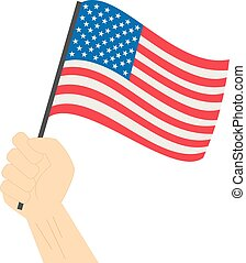 Hand holding and raising the national flag of United States of America