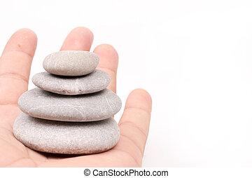 Hand holding balanced grey stones over white background
