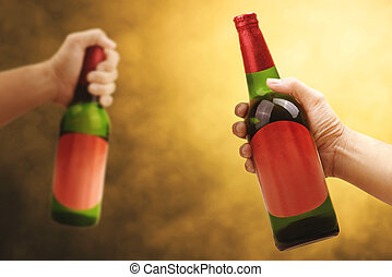 Hand holding beer bottle with a yellow background