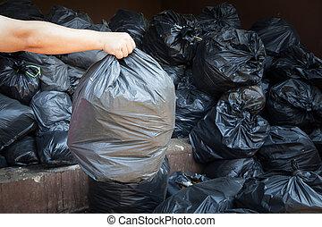 hand holding black trash bags
