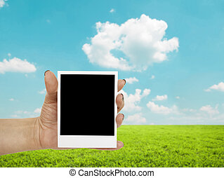 Hand holding blank photograph with landscape in background