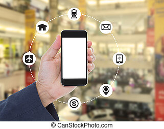 Hand holding blank screen mobile phone on blurred shopping mall background