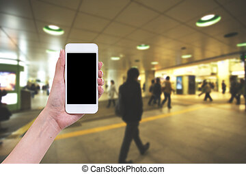 Hand holding blank screen mobile phone with blur business graphic background