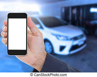 Hand holding blank screen mobile phone with blur car background