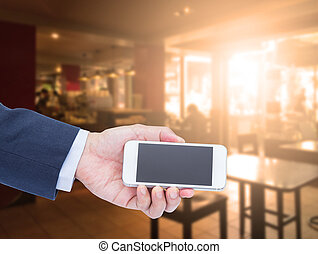 Hand holding blank screen mobile phone with blur coffee shop background