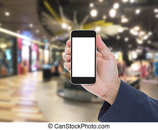 Hand holding blank screen mobile phone with blur shopping mall background